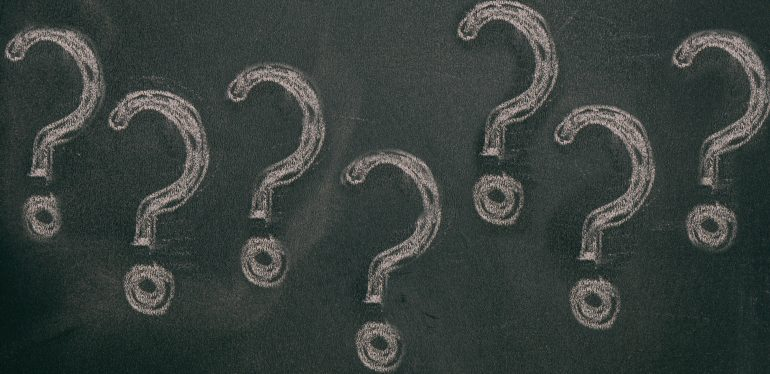 Question marks chalk drawing on blackboard background